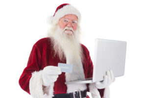 Blog image Santa pays with credit card on a laptop on white background