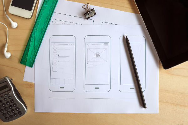 Blog image papers with sketches of a phone on a desk