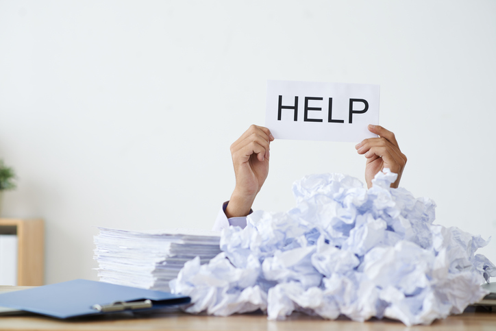 Blog image person under heap of crumpled papers with hand holding a help sign