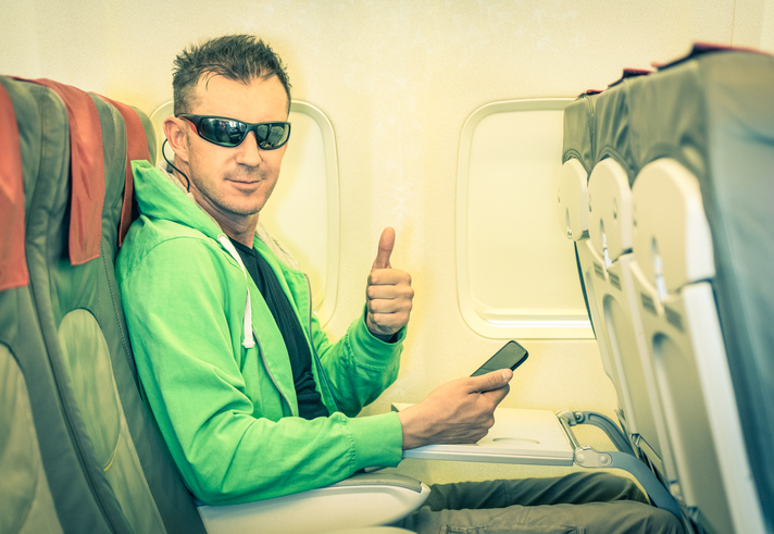 Blog image Young hipster man passenger satisfied with thumbs up inside airplane