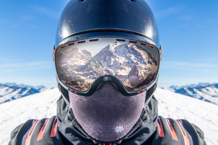 Blog image Reflection of spectacular snow covered mountain in skier goggles