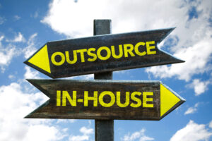 Blog image outsource and in-house wooden sigh on a post with sky background