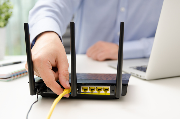 Blog image man plugs ethernet cable into router