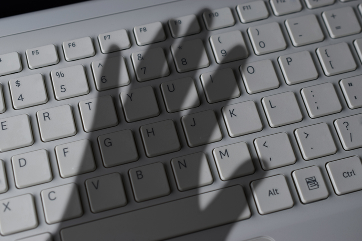 Blog image shadow of a hand over a white keyboard