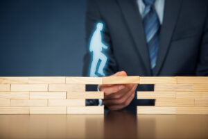 Blog image business man in the background holding a wooden block for a digital man to cross over