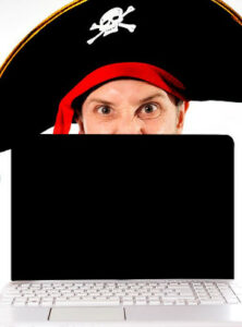 Man in pirate hate behind laptop computer